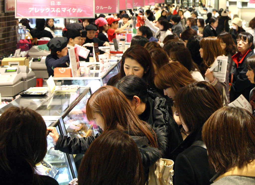 """Customers shop for chocolates at a sale ahead of Valentine's Day in an Isetan department store in Tokyo, Japan, on Monday, Feb. 7, 2011. Japan differs from many countries that mark today's annual celebration of love because it's women who offer chocolates to men. Under the tradition of """"giri choco,"""" which means chocolate as an obligation or duty, the gifts can signal love, or simply respect for male friends and colleagues. Photographer: Tomohiro Ohsumi/Bloomberg"""